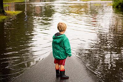 Caucasian boy wearing puddles near flood - p555m1311556 by Roberto Westbrook
