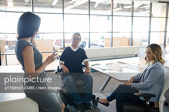Businessman in wheelchair with female colleagues in office meeting - p1192m2123385 by Hero Images