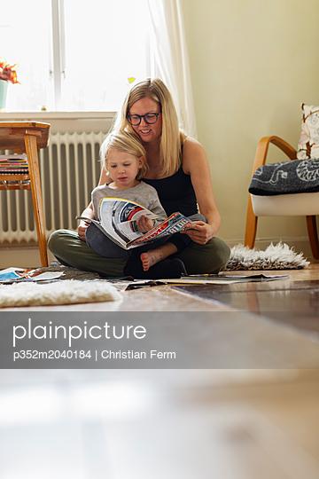plainpicture - plainpicture p352m2040184 - Mother and her son reading ... - plainpicture/Folio Images/Christian Ferm