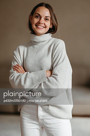 Junge Frau lächelt zufrieden in die Kamera - p432m2293182 von mia takahara