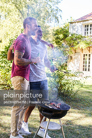 Young men with beer bottles standing near barbecue grill - p623m2294758 by Frederic Cirou