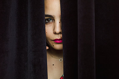 Woman peering through curtain - p1150m2176232 by Elise Ortiou Campion
