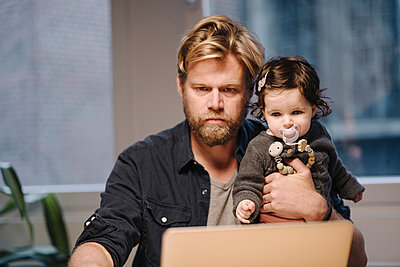 Casual businessman with daughter using laptop in office - p300m2167342 by Kniel Synnatzschke