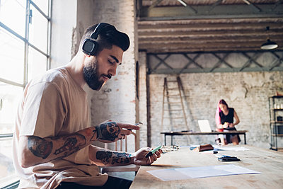 Creative young businessman with headphones and smartphone in loft office - p300m2202847 by Eugenio Marongiu
