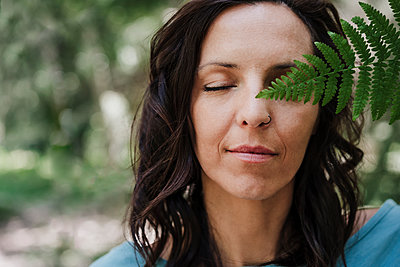 Woman with eyes closed holding fern leaf in forest - p300m2293436 by Eva Blanco