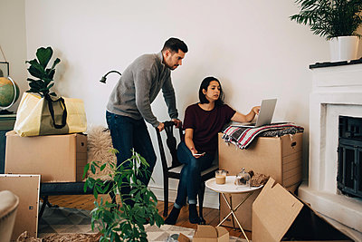 Woman showing laptop to man while moving at new home - p426m1542780 by Maskot
