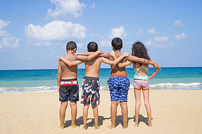 Four kids standing on the beach  - p794m1425486 by Mohamad Itani