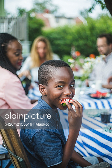 Smiling boy eating watermelon while sitting with family at table in garden - p426m2135516 by Maskot