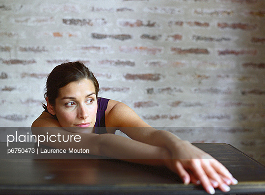 Young woman slouching on table - p6750473 by Laurence Mouton