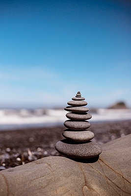 Stack of stones on rock against blue sky - p1166m1054313f by Nick Roush