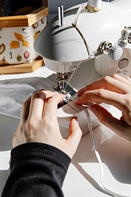 Crop seamstress using sewing machine in workshop - p1166m2193837 by Cavan Images