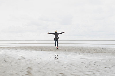 Netherlands, Ouddorp, back view of woman with arms outstretched standing on the beach in autumn - p300m2041665 by Christophe Papke