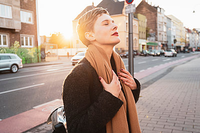 Woman on sidewalk with eyes closed, Cologne, Nordrhein-Westfalen, Germany - p429m2077829 by Tamboly