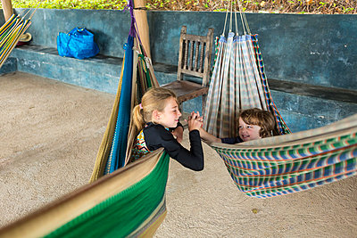 Caucasian brother and sister laying in hammocks holding hands - p555m1305335 by Marc Romanelli