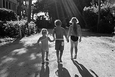 Children in swimsuits holding hands outdoors - p555m1418844 by Marc Romanelli