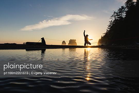 Slacklinerbalancing over coastal water, La Push, Washington, USA - p1166m2201619 by Evgeny Vasenev