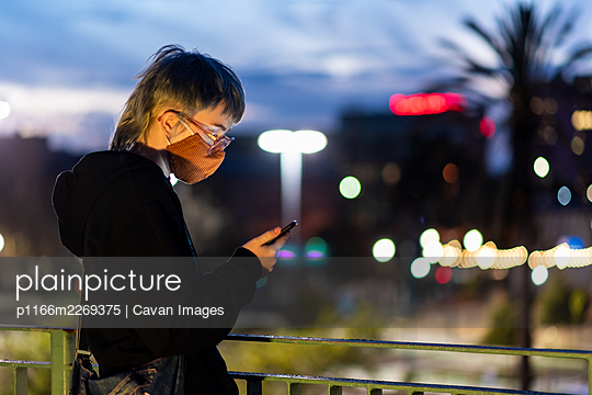 Teen with glasses looking at phone wearing mask in city setting - p1166m2269375 by Cavan Images