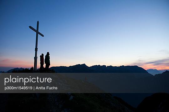 Austria, Tyrol, two hikers standing at summit cross - p300m1549519 by Anita Fuchs