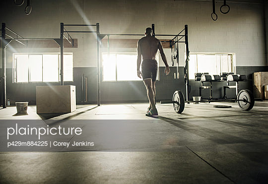 Young man preparing for exercise bar in gymnasium - p429m884225 by Corey Jenkins