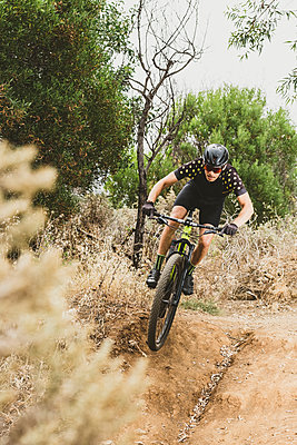Full body of mountain bike cyclist doing a jump in forest, vertical - p1166m2124115 by Cavan Images