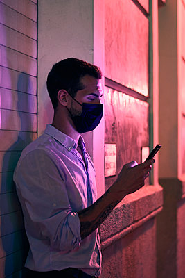 Young man with a mask looks at his mobile phone at night - p1166m2205779 by Cavan Images