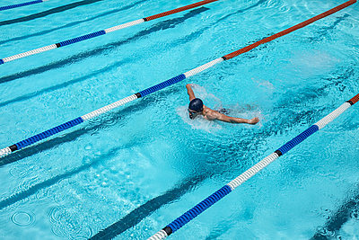 Young swimmer swimming butterfly stroke in swimming pool - p1315m2091043 by Wavebreak