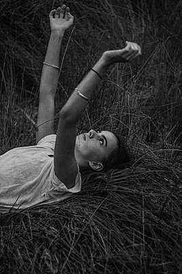 Young woman lying in grass - p1640m2259952 by Holly & John