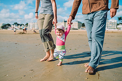 France, La Baule, baby girl walking on the beach with father and grandfather - p300m2005621 von Gemma Ferrando