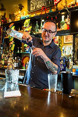 Barman preparing cocktail at public house counter - p924m1206455 by Steve Prezant