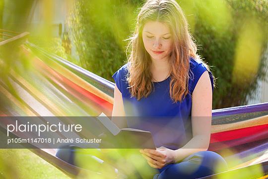 Junge Frau liest ein Buch auf einer Hängematte - p105m1147018 von André Schuster