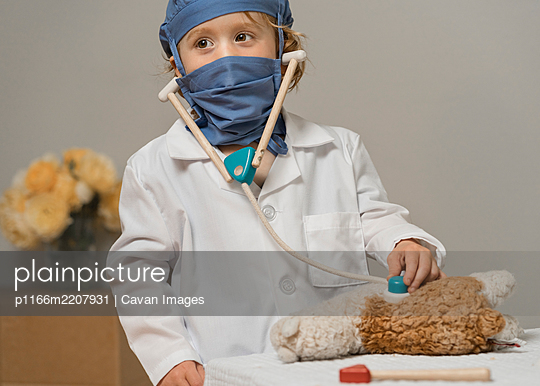 young child in medical PPE examines a plush toy lama - p1166m2207931 by Cavan Images