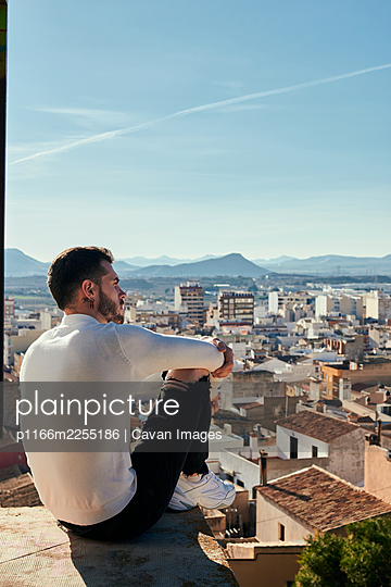 Man is sitting on a rooftop overlooking the city - p1166m2255186 by Cavan Images