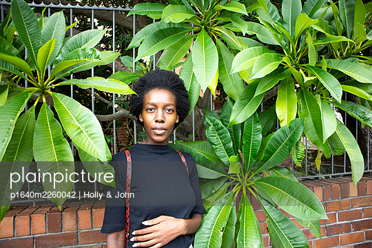 African woman in front of green leaves, portrait - p1640m2260042 by Holly & John