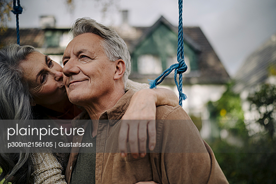 Happy woman hugging an kissing senior man on a swing in garden - p300m2156105 by Gustafsson