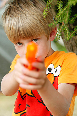 Boy playing with a water gun - p249m945103 by Ute Mans