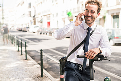 Smiling young businessman with e-scooter on the phone in the city, Lisbon, Portugal - p300m2144882 by Uwe Umstätter