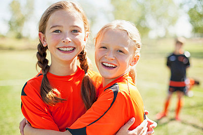 Girl soccer players smiling and hugging. - p328m783944f by Hero Images