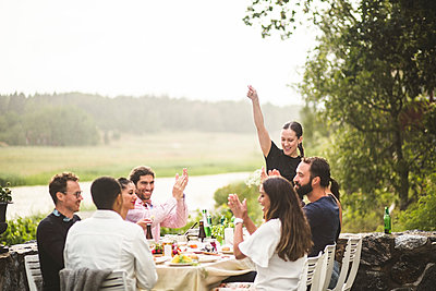 Mid adult woman standing with arm raised while friends applauding at table during dinner party in backyard - p426m2035680 by Maskot