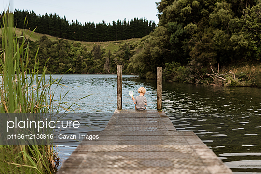 Young child holding a net at the end of a pier on a lake - p1166m2130916 by Cavan Images