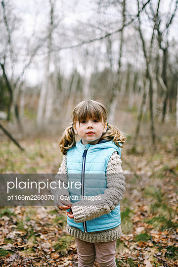 Little girl standing in the woods in spring wearing a light teal vest - p1166m2268870 by Cavan Images