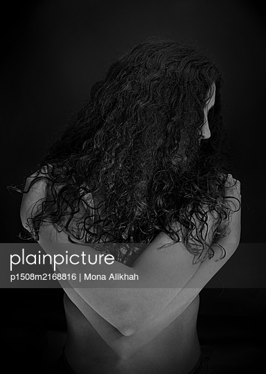 Rear view of woman with curly hair - p1508m2168816 by Mona Alikhah