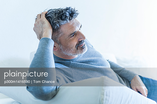 Relaxed mature man at home lying on couch