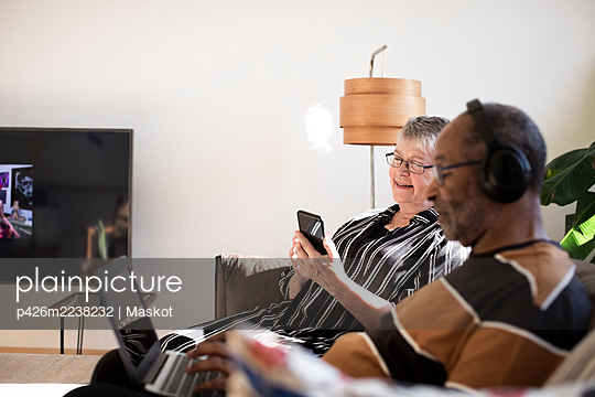 Woman using smart phone sitting by man with laptop at home - p426m2238232 by Maskot