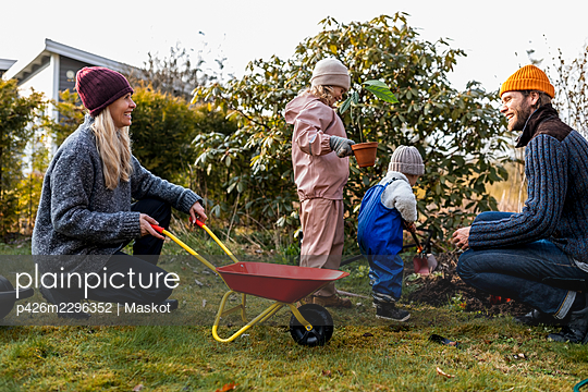 Happy family doing gardening together at back yard - p426m2296352 by Maskot