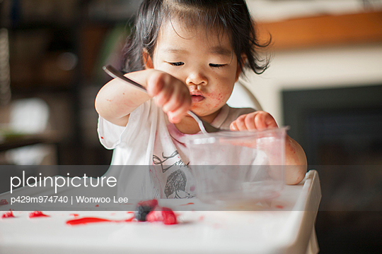 One year old baby girl eating fruit in highchair - p429m974740 by Wonwoo Lee