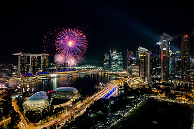Illuminated cityscape and fireworks against sky at night - p1166m1142544 by Cavan Images