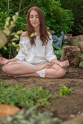 Young woman meditating in a woodland stumpery with a laughing Buddha in the background - p1433m1585142 by Wolf Kettler