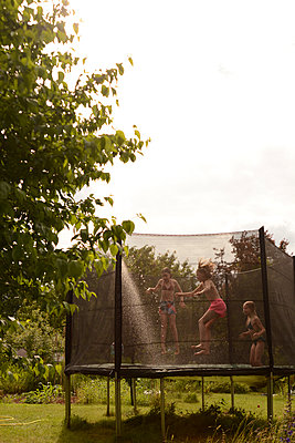 Kinder auf dem Trampolin - p262m1176725 von Philine Stehling