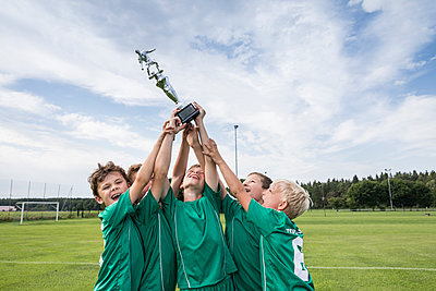 Young football players cheering with cup - p300m1581631 von Fotoagentur WESTEND61