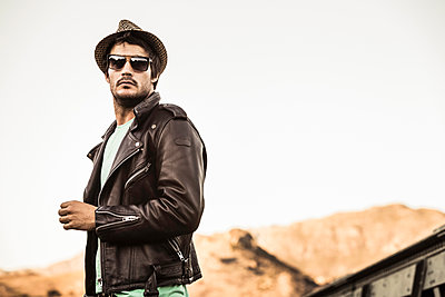 Portrait of stylish man wearing hat, sunglasses and leather jacket - p300m2181174 by Floco Images